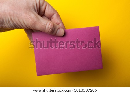 Hand holding a blank flyer, A6 flyer, postcard, invitation mock-up on a yellow background. #1013537206
