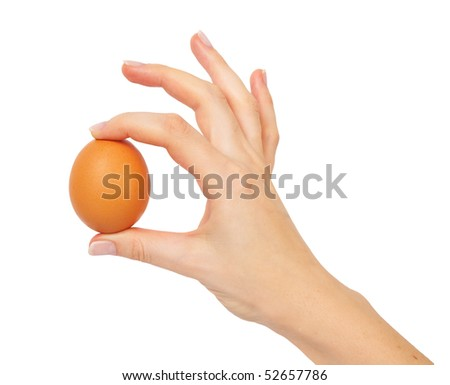 Hand holding a brown egg, isolated on white background
