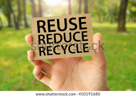 Hand holding a brown recycled paper card with Reuse Reduce Recycle word on abstract nature background