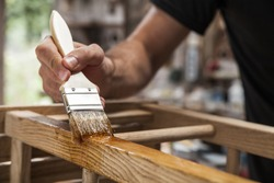 hand holding a brush applying varnish paint on a wooden furniture