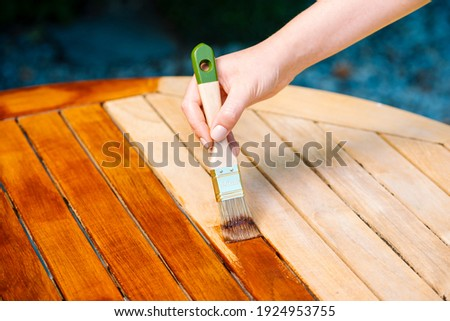 hand holding a brush applying varnish paint on a wooden garden table - painting and caring for wood with oil Foto d'archivio ©