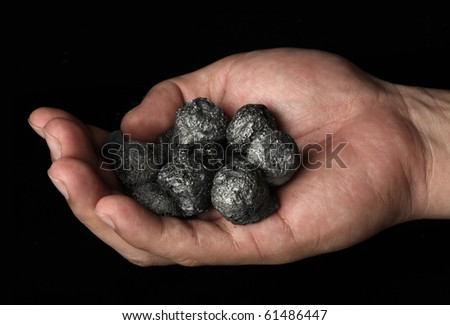Hand holding a bunch of coal