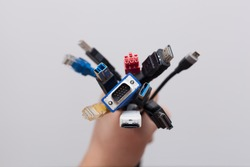 Hand holding a bunch of computer cables with different connectors