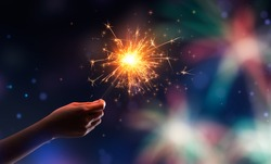 Hand holding a burning sparkler against fireworks background