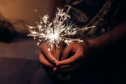 hand holding a burning sparkler firework bengal light. space for text. burning sparkler closeup in female hand in dark. happy new year and merry christmas concept. happy holidays