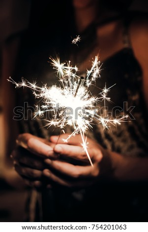 hand holding a burning sparkler firework bengal light. space for text. burning sparkler closeup in female hand in dark. happy new year and merry christmas concept. happy holidays #754201063