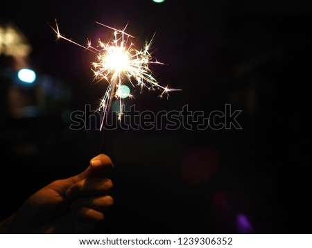 Hand holding a burning sparkler firework, Happy new year and Merry christmas concept, Happy holidays, Female hand holding a burning sparkler, Abstract blurred of Sparklers for celebration. #1239306352