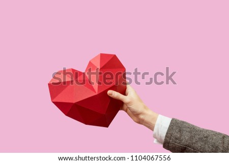 Hand holding a cardboard heart on a pink background. #1104067556