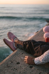 Hand holding a cigarette sitting on a stone ledge with pink shoes by the sea