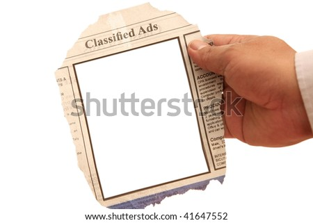 Hand holding a classified ads- many uses in the employment and resources.