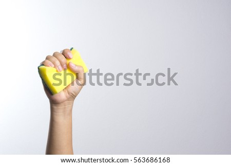 Hand holding a cleaning sponge on a white background #563686168