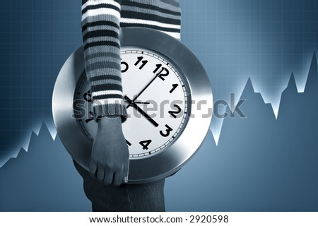 Hand holding a clock with a financial statistics on the background