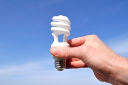 Hand Holding a Compact Fluorescent Light (CFL) Against a Blue Sky