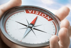 Hand holding a compass with needle pointing the word vision. Company or organization Statement values. Composite image between a hand photography and a 3D background.