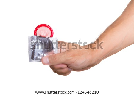 Hand holding a condom in package, isolated on white background