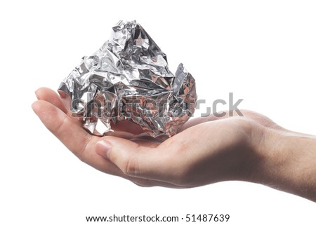 Hand holding a crumpled aluminum foil wrap