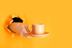 Hand holding a cup of coffee through a hole in torn saffron or light orange paper wall. Coffee break concept, copy space, minimalism