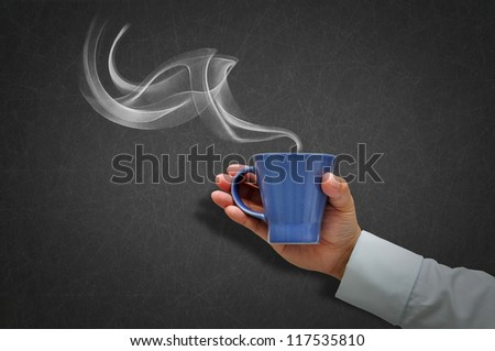 Hand holding a cup of coffee with white smoke
