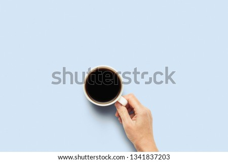 Hand holding a cup with hot coffee on a blue background. Breakfast concept with coffee or tea. Good morning, night, insomnia. Flat lay, top view