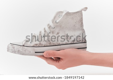 Hand holding a dirty canvas sneaker on white background. Shoes are needed cleaning. Care for footwear. Photo stock ©