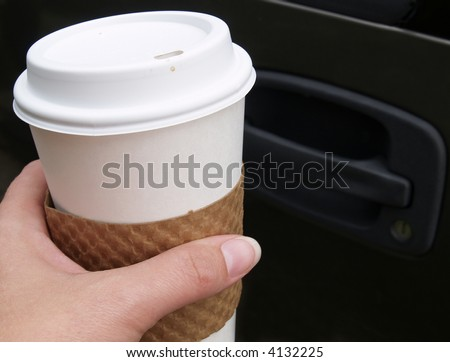 hand holding a disposable coffee cup outside of a car