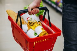 Hand holding a full basket of groceries in a supermarket. Young man with shopping basket full of different products in supermarket, closeup. shopping cart with products