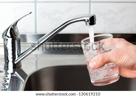 Hand holding a glass of water poured from the kitchen faucet.
