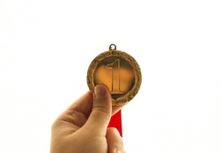 hand holding a gold medal on a white background, isolated