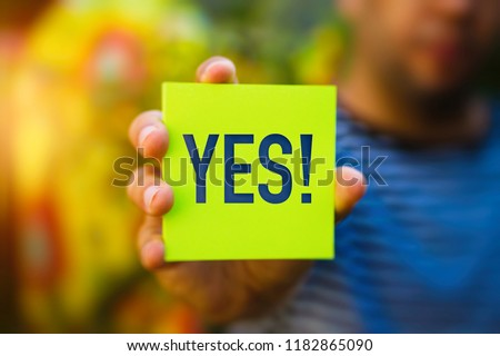 Hand holding a green Paper with the word YES against blurred background - Why?, Business Concept