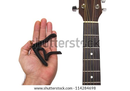 hand holding a guitar capo