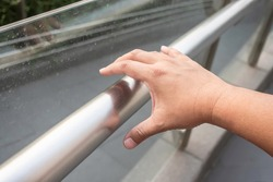 Hand holding a handle bar, The germ spread from person to person through direct physical contact