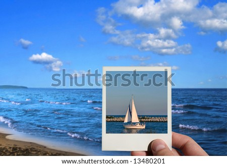 hand holding a holiday photo, beautiful seashore in background, photo inside is my property - stock photo