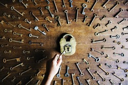 Hand holding a key to unlock a lock