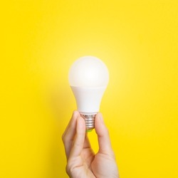 Hand holding a LED light bulb on bright yellow background. Using economical and environmentally friendly light bulb concept. Idea concept. Energy saving lamp in woman's hand.