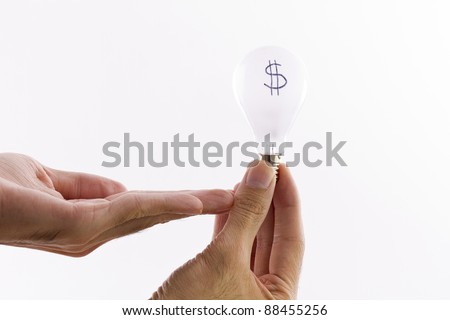 hand holding a lightbulb, dollar sign written on lightbulb representing the cost of electricity or cost of necessities. - ecology oriented