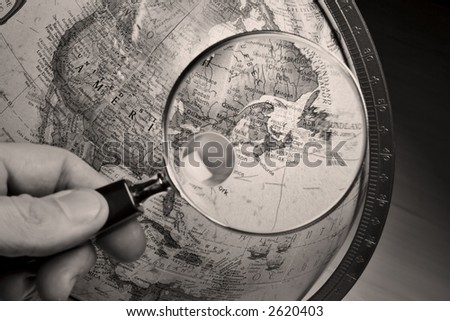 Hand holding a magnifying glass above an earth globe.