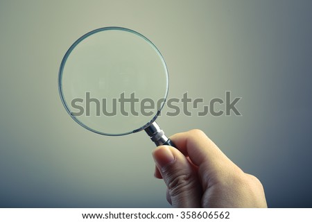 Hand holding a magnifying glass with blank background.