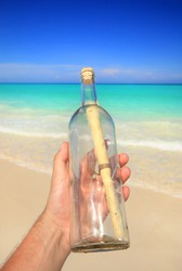 Hand holding a message in a bottle found on a tropical beach