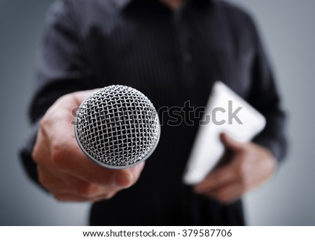 Hand holding a microphone conducting a business interview or press conference