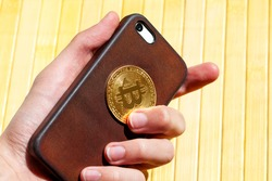 Hand holding a modern smartphone and a golden bitcoin coin symbol. E-commerce, earning with mobile crypto currency trading apps, phone bit wallet abstract concept, wealth. Buying and selling btc