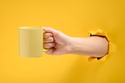 Hand holding a mug of cofee through torn yellow paper background. Have a break and refreshing drink.