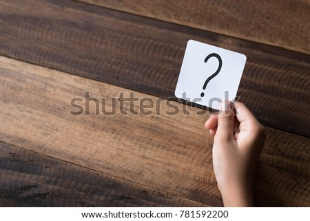 hand holding a note written a question mark on a wooden table background #781592200