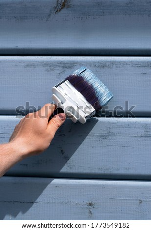 Hand holding a paintbrush towards wooden house wall