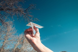 Hand holding a paper airplane, origami with a background of blue sky