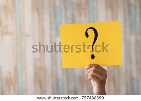 hand holding a paper note with question mark.question mark written on paper #757486390