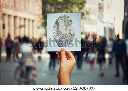 Hand holding a paper sheet with fingerprint icon over a crowded street background. Concept of social identity and privacy. Personal private data diversity symbol, identification process and security.