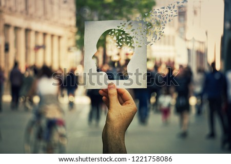 Hand holding a paper sheet with human head icon broken into pieces over a crowded street background. Concept of memory loss and dementia disease. Alzheimer's losing brain and memory function. #1221758086