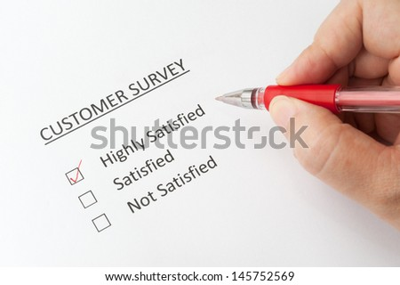 Hand holding a pen and filling a  customer survey with options of highly satisfied, satisfied and not satisfied - stock photo