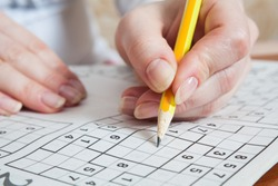 Hand Holding a Pen Playing Sudoku