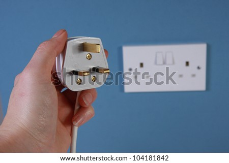Hand holding a 3 pin plug with socket in the background on a blue wall.  This is a United Kingdom 3 pin plug